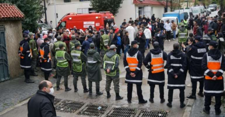 Emergency services in Morocco's port of Tangiers gather at the site where at least 24 people died when their underground textile workshop was flooded on Monday.  By - (AFP)