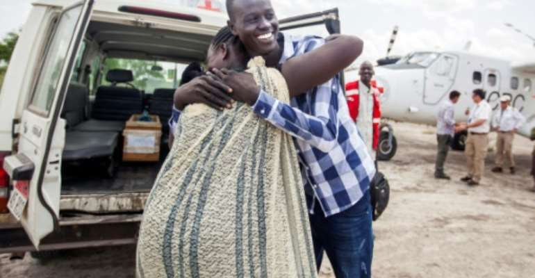 Emmanuel, 17, hugs his mother as they reunite after more than three years, forced apart by South Sudan's civil war which began in 2013.  By ALBERT GONZALEZ FARRAN (AFP)