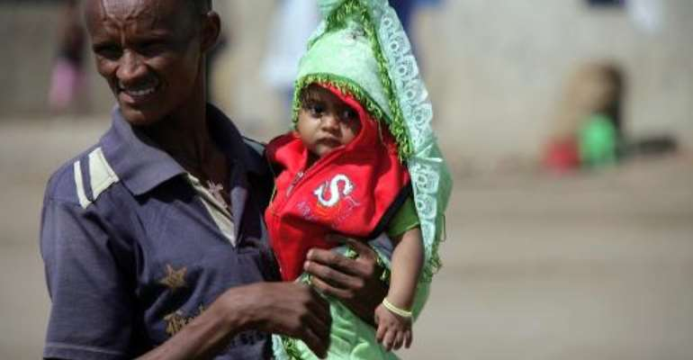 An Eritrean refugee holds his child at Sudan's Shagarab refugee camp in Kassala on January 12, 2012.  By Ashraf Shazly (AFP/File)
