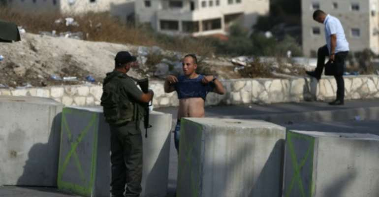 An Israeli border guard inspects a Palestinian man at a newly erected checkpoint at the exit of the east Jerusalem neighborhood of Issawiya on October 19, 2015.  By Ahmad Gharabli (AFP)