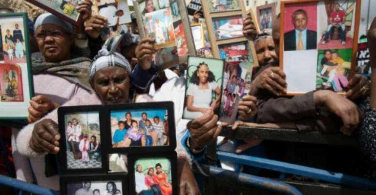 Israelis from the Ethiopian community hold up photographs of their relatives in front of Israel's Prime Minister's office in Jerusalem on March 20, 2016.  By Menahem Kahana (AFP)