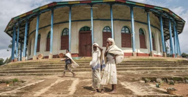 Ethiopian Orthodox devotees stand outside a church in Anderacha, once the site of a palace of the Kaffa kingdom near the town of Bonga in southern Ethiopia.  By EDUARDO SOTERAS (AFP)