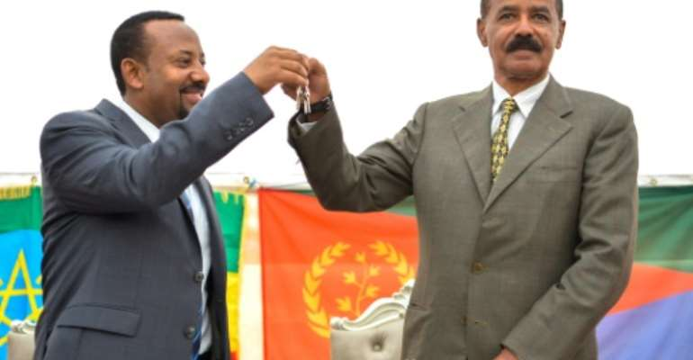 Ethiopian Prime Minister Abiy Ahmed (left) and Eritrean President Isaias Afwerki celebrate the reopening of the Embassy of Eritrea in Ethiopia in Addis Ababa on July 16, 2018.  By MICHAEL TEWELDE (AFP/File)