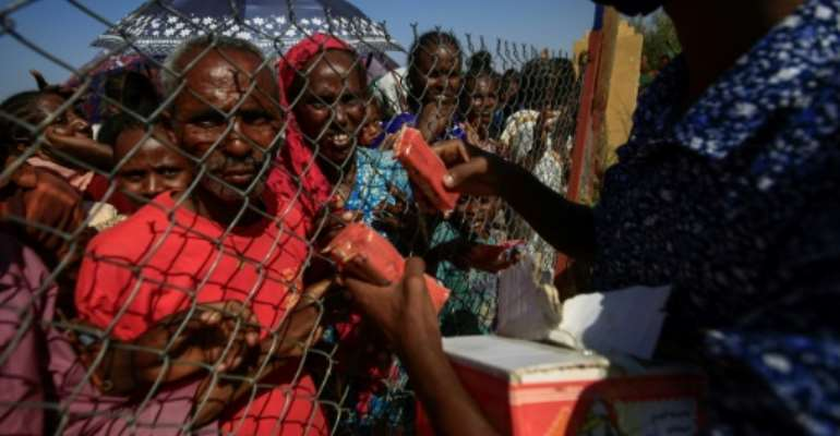 Ethiopian refugees who fled fighting in the Tigray region receive food at the 'Village 8' reception center in Sudan's eastern Gedaref state.  By ASHRAF SHAZLY (AFP)
