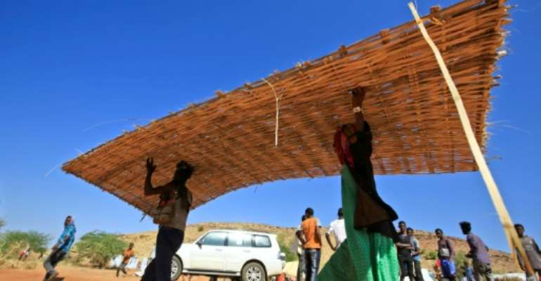 Ethiopian refugees who fled the Tigray conflict build huts in Sudan's Um Raquba camp.  By ASHRAF SHAZLY (AFP)