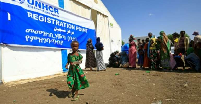 Ethiopian refugees, who have fled the Tigray conflict, queue for food outside UNHCR and World Food Programme tents at a transit centre in Sudan's border town of Hamdayit.  By ASHRAF SHAZLY (AFP)