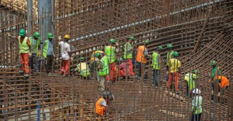 Ethiopian workers stand on scaffolding in 2015 during the construction of the Grand Renaissance Dam.  By ZACHARIAS ABUBEKER (AFP/File)