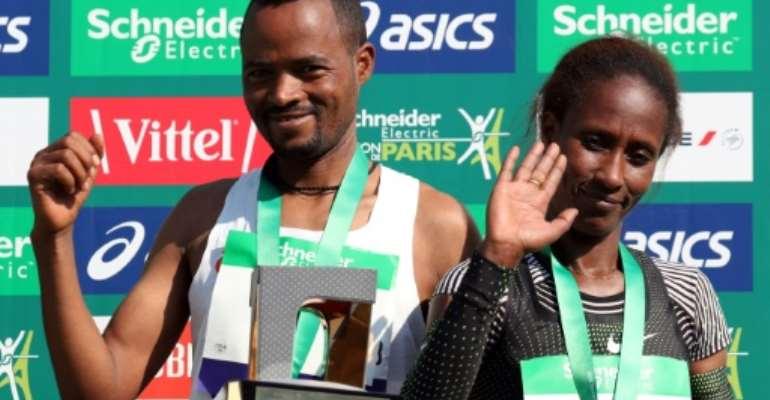 Ethiopia's Abrha Milaw and Gelete Burka celebrate their victories in the Paris marathon.  By KENZO TRIBOUILLARD (AFP)