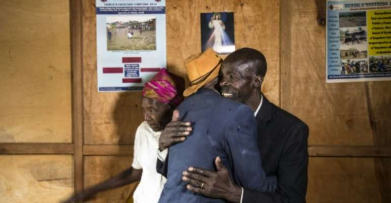 Ethnic Tutsi Jean-Bosco Gakwenzire (in the hat), 65, embraces Pascal Shyirahwamaboko, 68, who was among the killers of his father at Mutete, where the old schoolfriends have now reconciled.  By JACQUES NKINZINGABO (AFP/File)