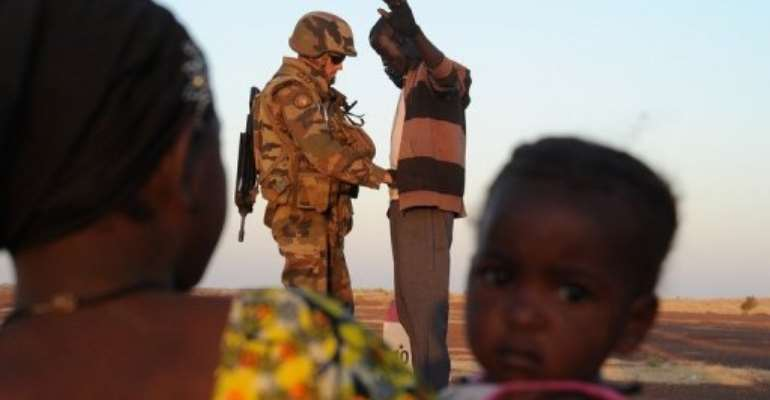 A woman and child watch a French soldier at a check point frisking a man trying to enter Gao, Mali on February 14, 2013.  By Pascal Guyot (AFP/File)