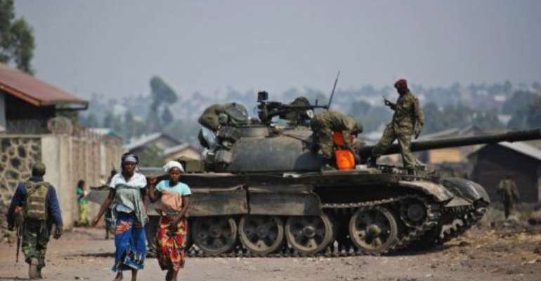 Two Congolese women walk past a government army tank in Munigi, on the outskirts of Goma on July 15, 2013.  By Phil Moore (AFP/File)