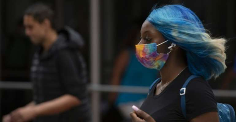Face masks are reappearing in cities around the world as the Delta variant fuels a surge in coronavirus cases.  By Kena Betancur (AFP)