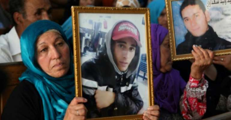 Families of victims of Tunisia's 2011 revolt against dictatorship carry portraits of their loved ones during a trial in Kasserine on July 13, 2018.  By HATEM SALHI (AFP/File)
