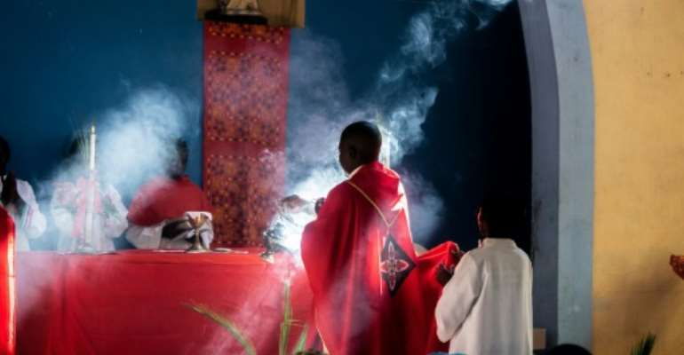 Father Celso Taibo burns incense during a palm Sunday mass in Buzi.  By Zinyange AUNTONY (AFP)