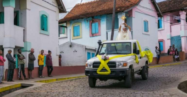 Father Pedro hopped on the back of a four-wheel drive and paraded through the town of Akamasoa.  By RIJASOLO (AFP)