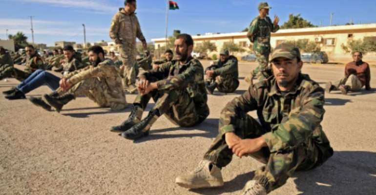 Fighters of a battalion loyal to Libyan General Khalifa Haftar pictured in the eastern city of Benghazi in December 2019. Both sides in Libya's conflict agreed to a ceasefire that started early Sunday.  By Abdullah DOMA (AFP/File)