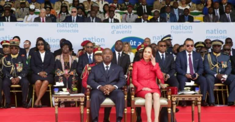 File picture from Gabon's independence day celebrations on August 17, with President Ali Bongo and his wife Sylvia sitting on the tribune and Bongo's chief of staff, Brice Laccruche Alihanga, seated behind them, second from right.  By Steve JORDAN (AFP/File)