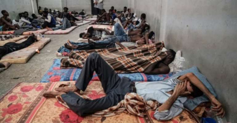 (FILES) In this file photo taken on June 17, 2017 illegal immigrants are seen sleeping at a detention centre in Zawiyah, 45 kilometres west of the Libyan capital Tripoli.   The heads of two refugee agencies have called for refugees and migrants held in Libyan centres to be freed and for countries to take them in.  By Taha JAWASHI (AFP/File)