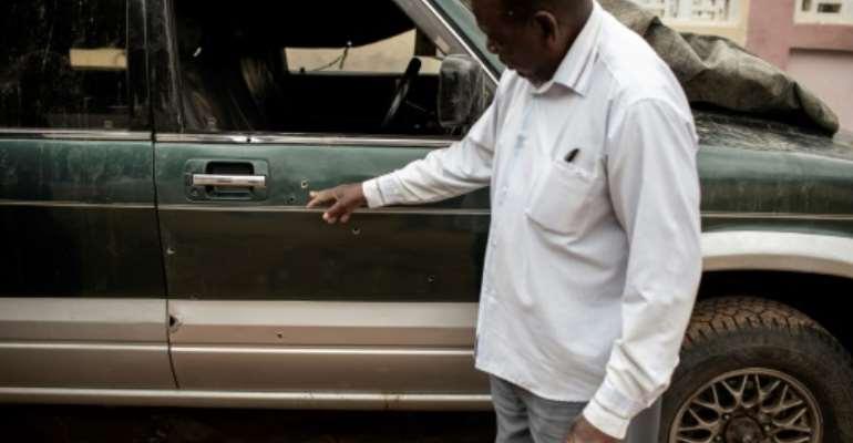 Filipe Mahanjane points to bullet holes in the car where election observer Anastacio Matavele was slain in Xai-Xai, Mozambique.  By GIANLUIGI GUERCIA (AFP)
