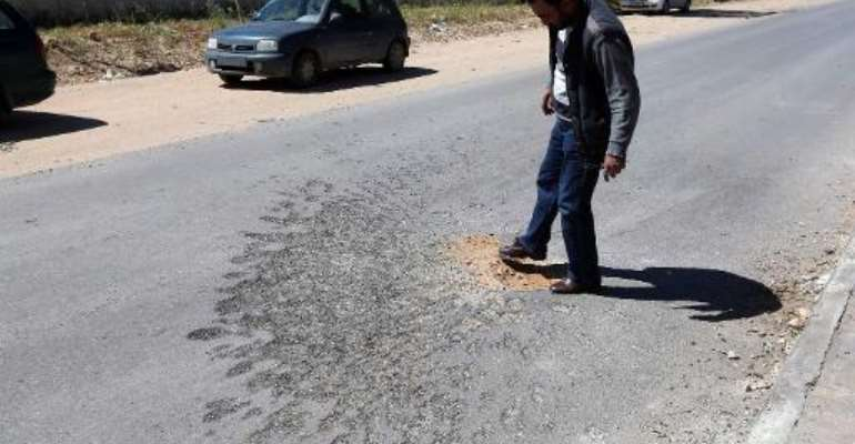 A Libyan man looks at traces on the ground after a rocket attack in Zawiya, 40 kilometres west of Tripoli, killed one Filipino oil worker and wounded five others on March 30, 2015.  By Mahmud Turkia (AFP)