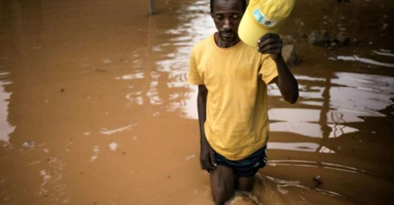 Fisherman Edouard walks among the flooded ruins of his house in Bangui.