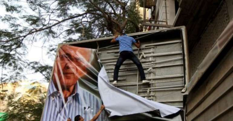 Egyptian protesters tear down a poster of presidential candidate Ahmed Shafiq in Cairo.  By Marwan Naamani (AFP)