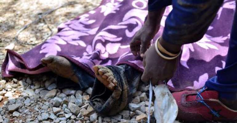 This file photo shows the body of an illegal miner lying on the ground after being pulled out of an illegal gold mine in Benoni, outside Johannesburg, on February 18, 2014.  By Mujahid Safodien (AFP/File)