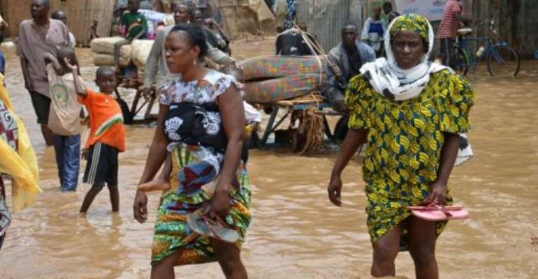 Residents walk in floodwaters as they evacuate Niamey after their homes were destroyed by floods on August 19, 2012.  By Boureima Hama (AFP/File)