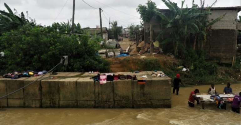 Floods are more frequent in a poor Douala neighbourhood where residents dried their belongings next to the river that flooded days earlier.  By Adrien MAROTTE (AFP)