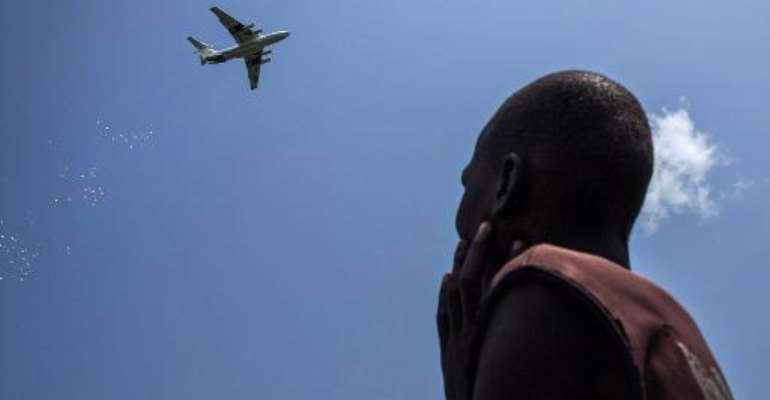 A man looks at an International Red Cross plane dropping emergency food supplies in Leer, South Sudan, on July 5, 2014.  By Nichole Sobecki (AFP/File)