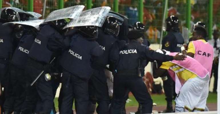 Ghana's national football team players leave the pitch protected by riot police at the half-time of the 2015 African Cup of Nations semi-final football match between Equatorial Guinea and Ghana in Malabo, on February 5, 2015.  By Issouf Sanogo (AFP)
