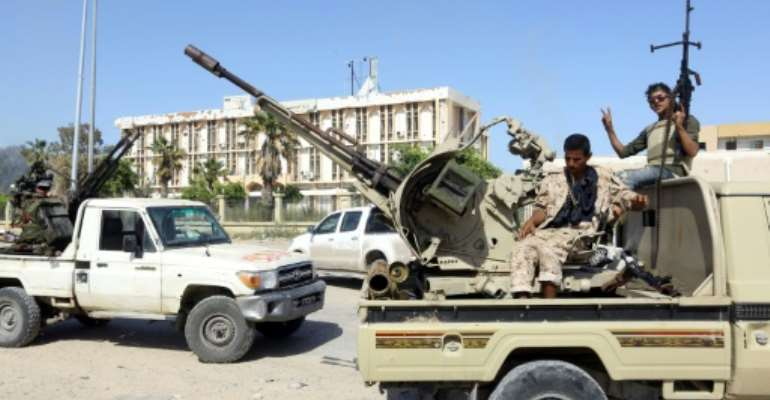 Forces loyal to Libya's Government of National Accord (GNA) gesture on April 18, 2019, after taking control of the Al-Aziziyah area south of the Libyan capital Tripoli, following fierce clashes with forces loyal to strongman Khalifa Haftar.  By Mahmud TURKIA (AFP)