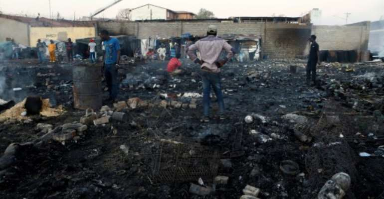 Foreigners in Marabastad, in the Pretoria area, try to save their belongings after their shacks were set alight in last month's attacks.  By Phill Magakoe (AFP)