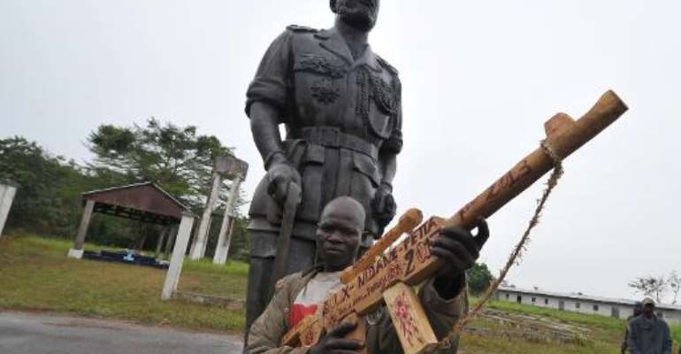 A former member of the Seleka rebel group poses with his wooden weapon next to a statue of the former Central African Republic Jean-Bedel Bokassa in Beringo, on March 3, 2014.  By Sia Kambou (AFP)