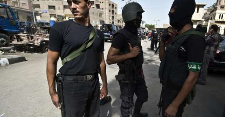 Egyptian armed policemen are deployed in a street during a raid in the village of Kerdassah on the outskirts of Cairo, on September 19, 2013.  By Khaled Desouki (AFP/File)