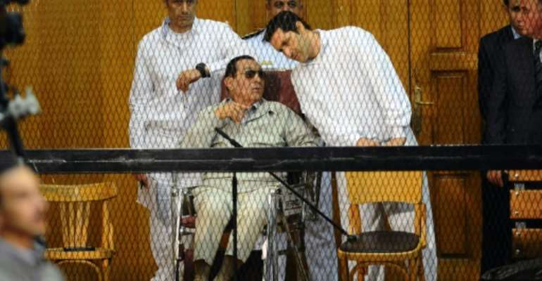 Former Egyptian president Hosni Mubarak with his two sons Alaa (R) and Gamal during their trial in Cairo in September 2013.  By AHMED EL-MALKY (AFP)