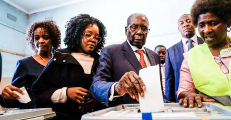 Former Zimbabwean president Robert Mugabe (C), his daughter Bona (C) and wife Grace (L) cast their votes at a polling station in the Highfields district of Harare.  By Zinyange AUNTONY (AFP)