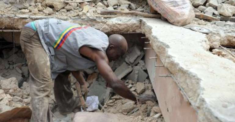Rescue workers remove a carpet from the rubble of a collapsed four-storey building at Idumota in Lagos on July 7, 2011.  By Pius Utomi Ekpei (AFP/File)