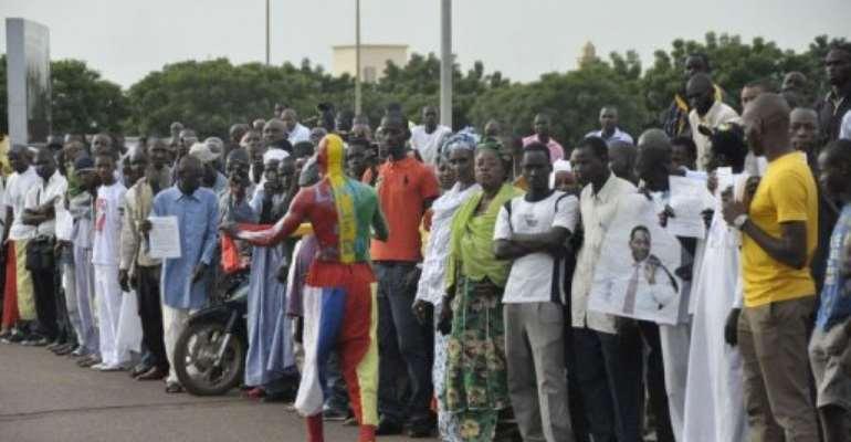 People await Mali's interim President Dioncounda Traore's arrival at Bamako airport.  By Habibou Kouyate (AFP/File)
