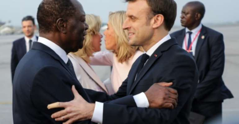 France's President Emmanuel Macron (R) was greeted by Ivory Coast's President Alassane Ouattara.  By LUDOVIC MARIN (AFP)