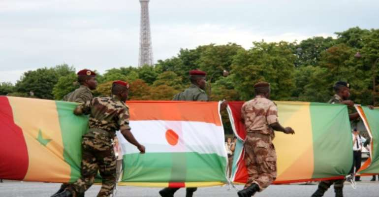French connection: Troops carry African flags -- with Niger's at centre -- at the 2010 Bastille Day parade in Paris.  By FLORE GIRAUD (AFP)