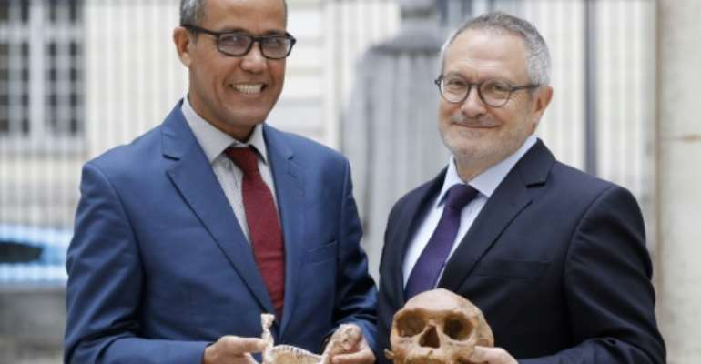French paleoanthropologist Jean-Jacques Hublin (R) and Abdelouahed Ben-Ncer of the National Institute of Archaeology and Heritage Sciences in Morocco pose with the casting of a skull of Homo Sapiens discovered in Morocco on June 6, 2017 in Paris.  By PATRICK KOVARIK (AFP)