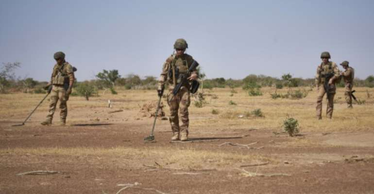 French soldiers use detectors while searching for IEDs (Improvised Explosive Devices), which kill scores each year in the jihadist-hit Sahel region.  By MICHELE CATTANI (AFP)