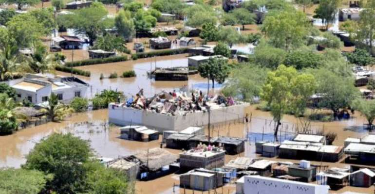 People camp on roofs in the devastated southern Mozambican town of Chokwe in a photo taken on January 25, 2013.  By  (Marcy Air switzerland/AFP/File)