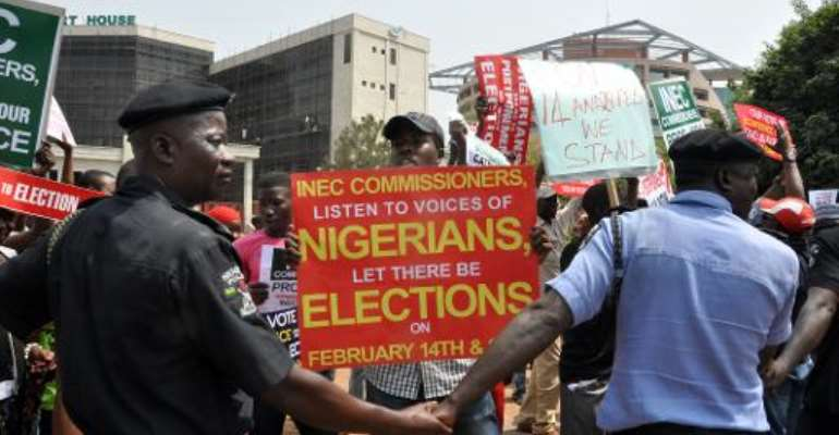 Police officers holds hands to block people holding sign protesting as chairman of the Independent National Electoral Commission  announced that Nigeria has postponed its presidential election.  By  (AFP/File)