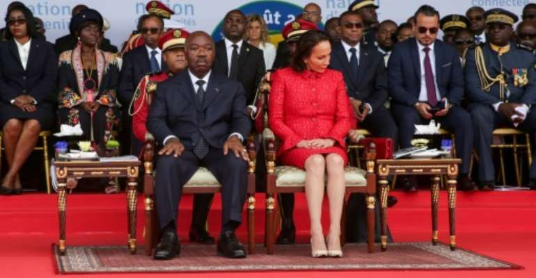 Gabon's President Ali Bongo and the First Lady attend a ceremony in August 2019. Bongo's then cabinet director Brice Laccruche Alihanga is second to the right behind the presidential couple.  By Steve JORDAN (AFP/File)