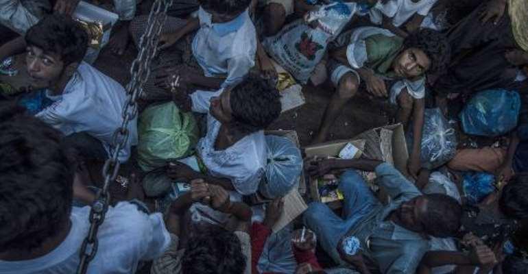 Myanmarese Muslim Rohingya residents sit inside a police truck in Birem Bayuen in Indonesia's East Aceh province on May 20, 2015.  By Sutanta Aditya (AFP)