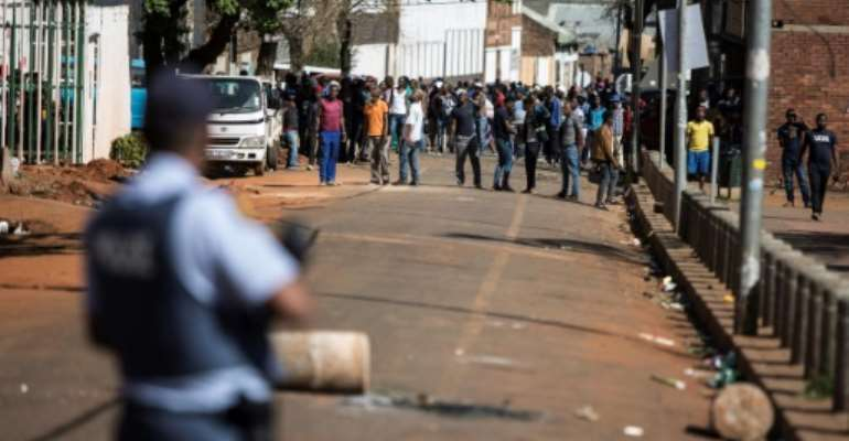 Gangs of aggressors armed with sticks and machetes attacked businesses in South Africa's financial capital last month during deadly xenophobic attacks.  By GUILLEM SARTORIO (AFP)
