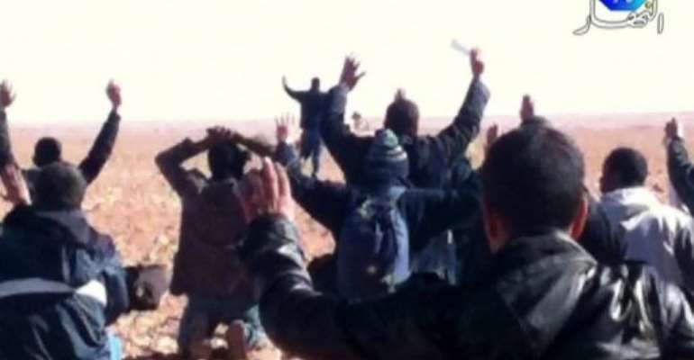 A still image broadcast by Algeria's Ennahar TV on January 19, 2013, shows hostages surrendering to Islamist gunmen.  By  (Ennahar TV/AFP/File)