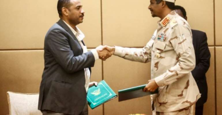 General Mohamed Hamdan Daglo (R), deputy head of Sudan's ruling military council, and protest movement leader Ahmed Rabie shake hands after signing the constitutional declaration at a ceremony in Khartoum.  By ASHRAF SHAZLY (AFP)